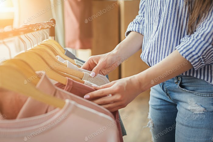 Smiling girl bying clothes in showroom