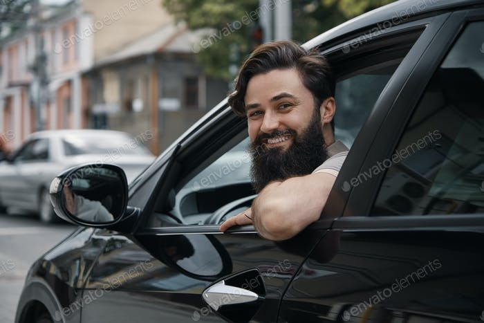 Young man smiling while driving a car