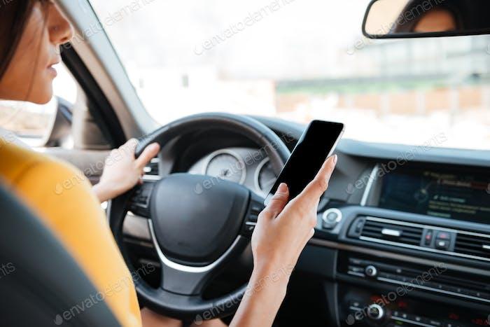 Молодая женщина водитель с помощью смартфона с сенсорным экраном