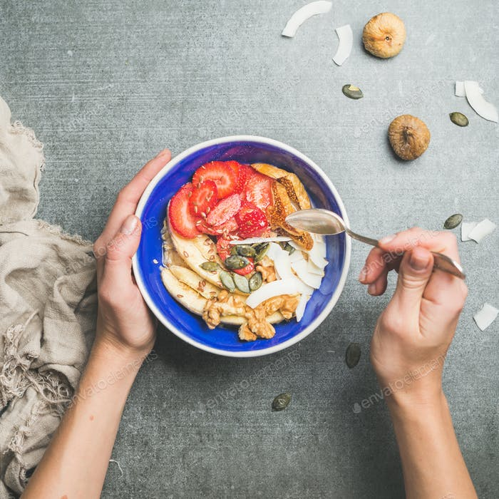 Woman's hands holding blue healthy breakfast bowl