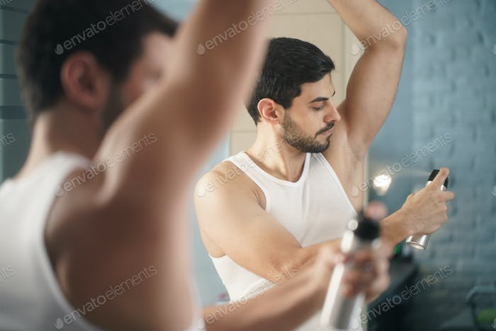 Man Using Spray Deodorant On Underarm For Bad Smell