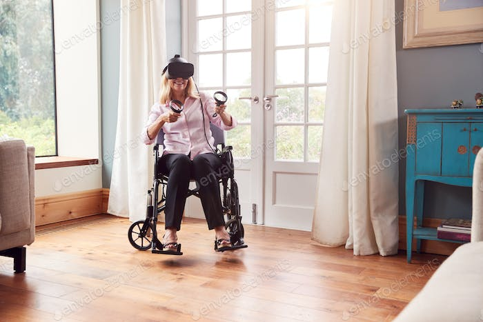 Mature Disabled Woman In Wheelchair At Home Wearing Virtual Reality Headset With Gaming Controllers
