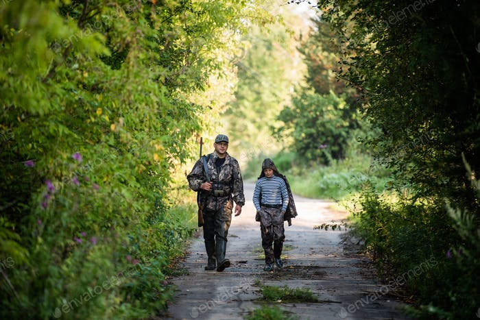 Father and son walking together outdoors with rifle for hunting