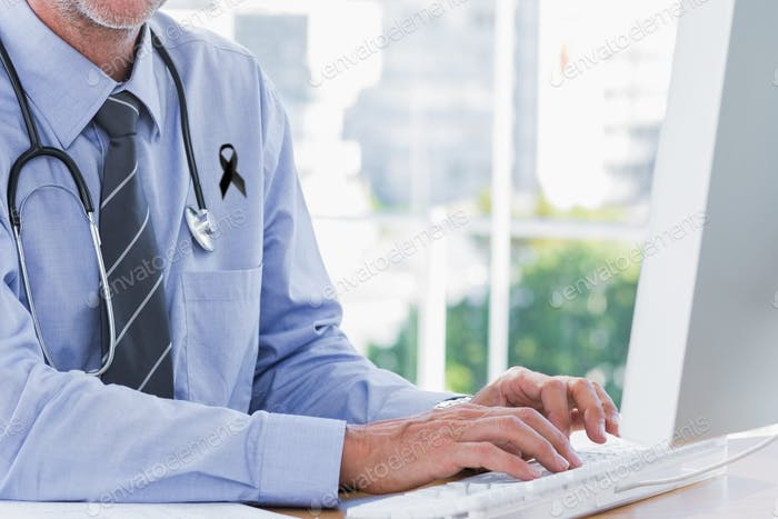 Mid section of male doctor with black ribbon on shirt using computer