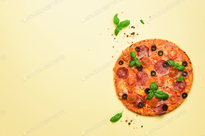 Delicious italian pizza, basil leaves, salt, pepper on yellow background with copyspace. Top view