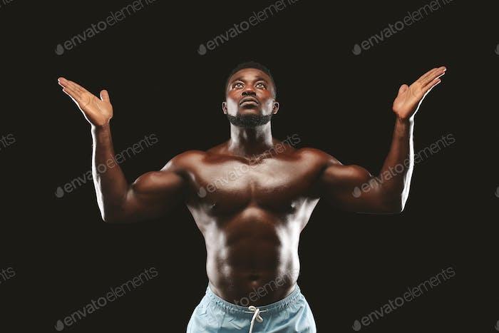Artistic black guy raising his hands up against black background