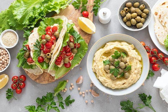 Tortilla Wraps mit Kichererbsenhummus, frischen Tomaten und Oliven, veganes Essen