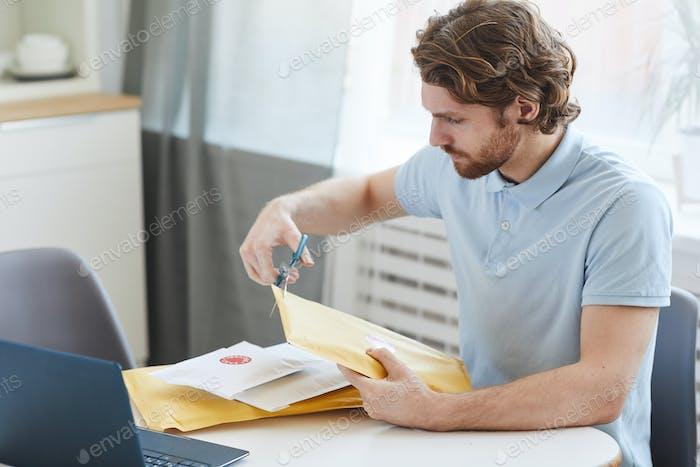 Man opening the envelopes