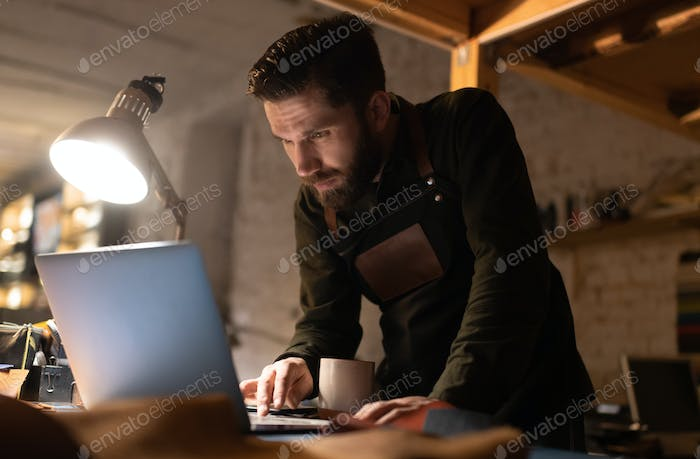 Artisan using laptop on table in workshop