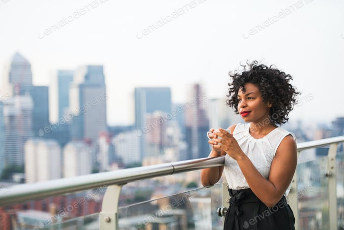 A portrait of a woman standing on a terrace, holding a cup of coffee.