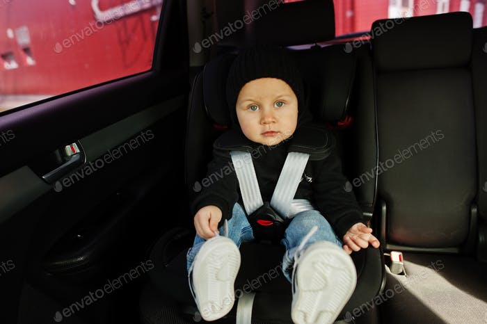 Сhild in car. Baby seat on chair. Safety driving concept.
