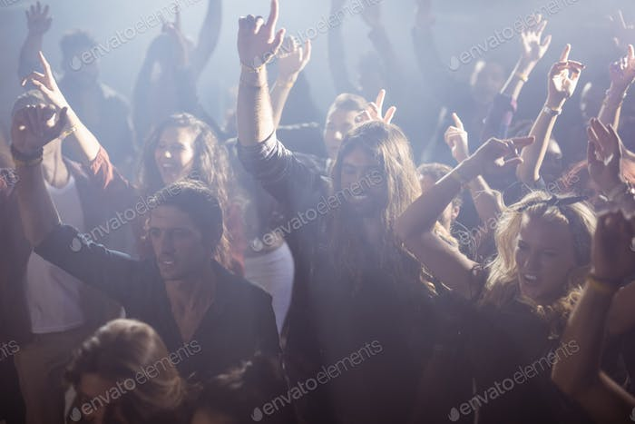 Cheerful fans dancing at nightclub during music festival
