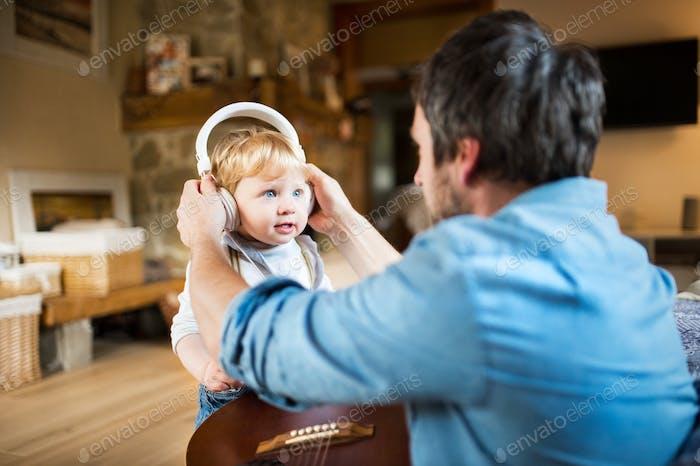 Vater und Sohn mit Smartphone und Ohrhörer, Musik hören.