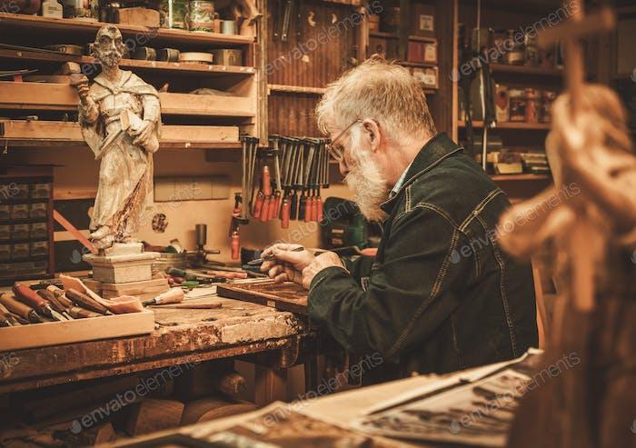 Senior restorer working with antique decor element in his workshop