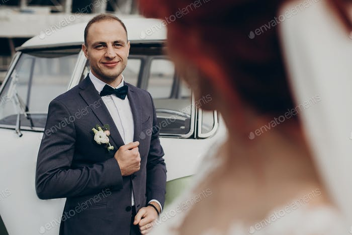 Stylish bride and groom sensually posing near retro car with boho bouquet