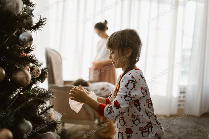 One little girl in pajama decorates a New Year's tree in the light cozy room