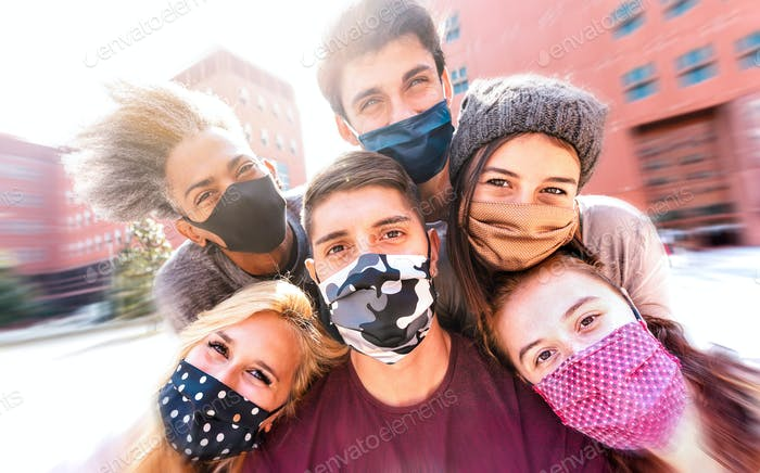 Multiracial friends taking selfie with face masks
