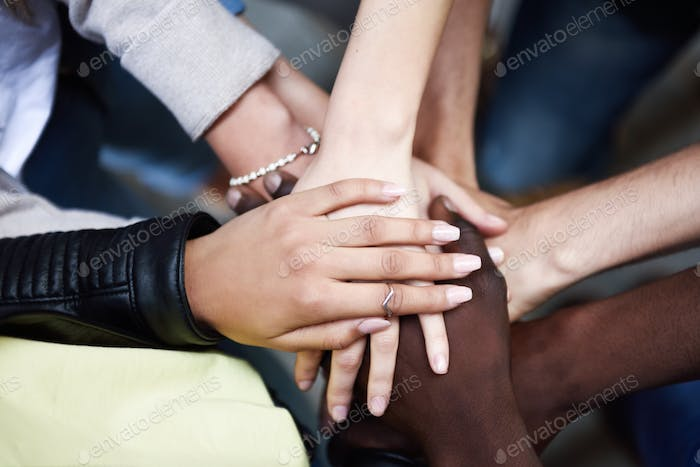 Top view of young people putting their hands together.