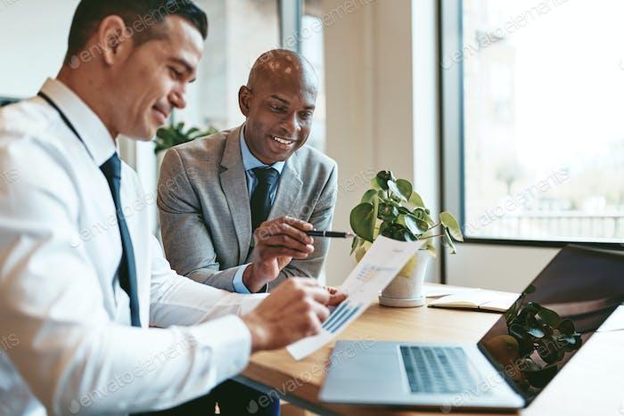 Zwei verschiedene Geschäftsleute gehen über Graphen zusammen in einem Büro
