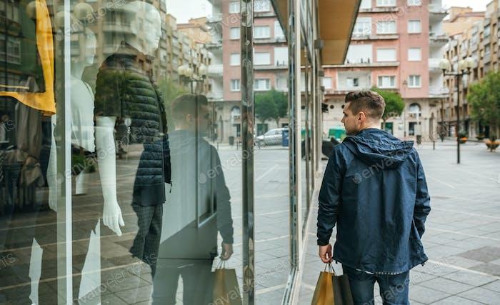 Mann mit Einkaufstaschen vor dem Bekleidungsgeschäft