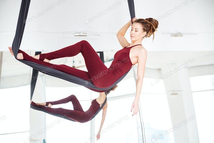 Pensive young woman doing antigravity yoga using hammock