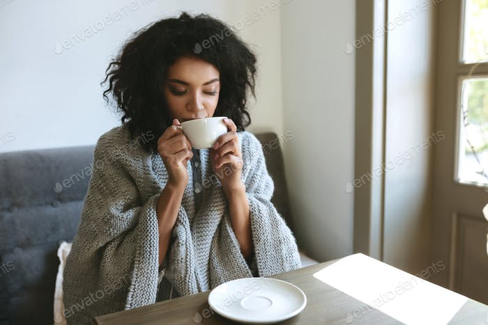 Portrait of young lady with dark curly hair dreamily closing her eyes with cup in hands