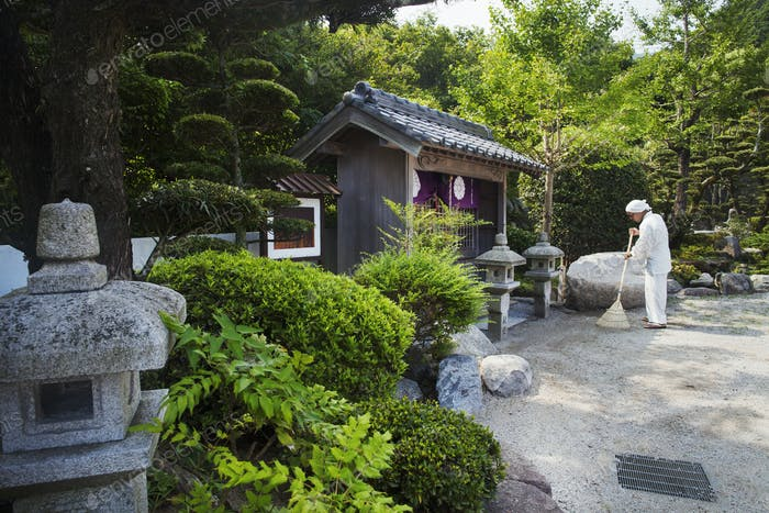 Buddhist monk by shrine in a temple garden, holding broom
