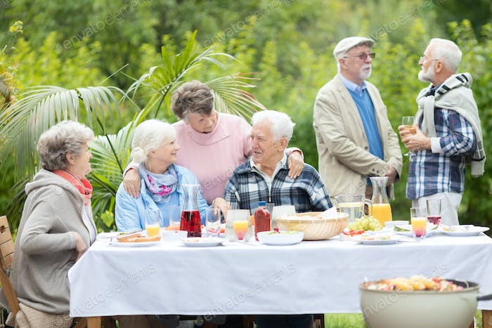 Cheerful group of elderly friends during barbeque at garden of family home