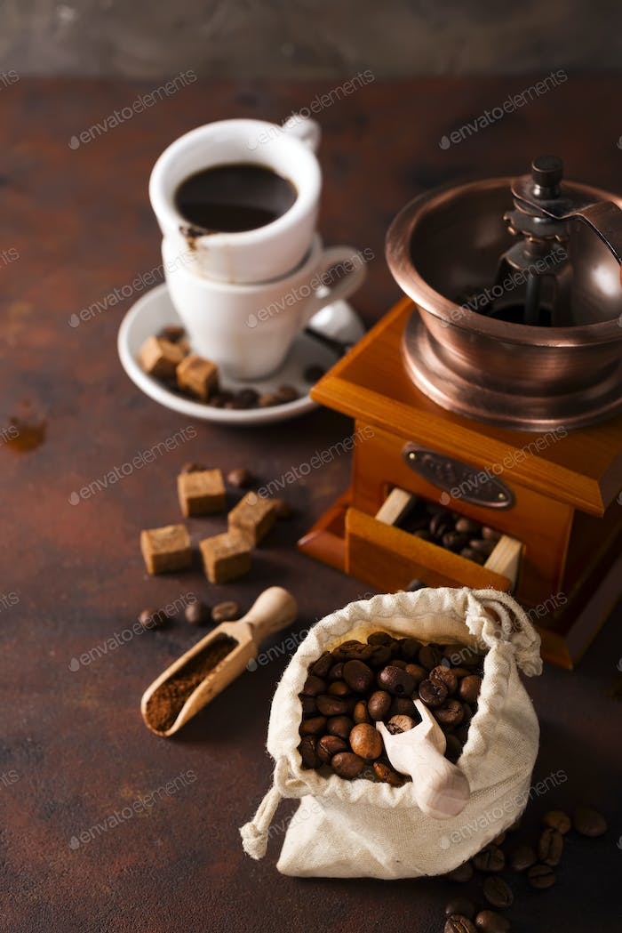 Coffee grinder , cup of coffee and coffee beans bag in background.