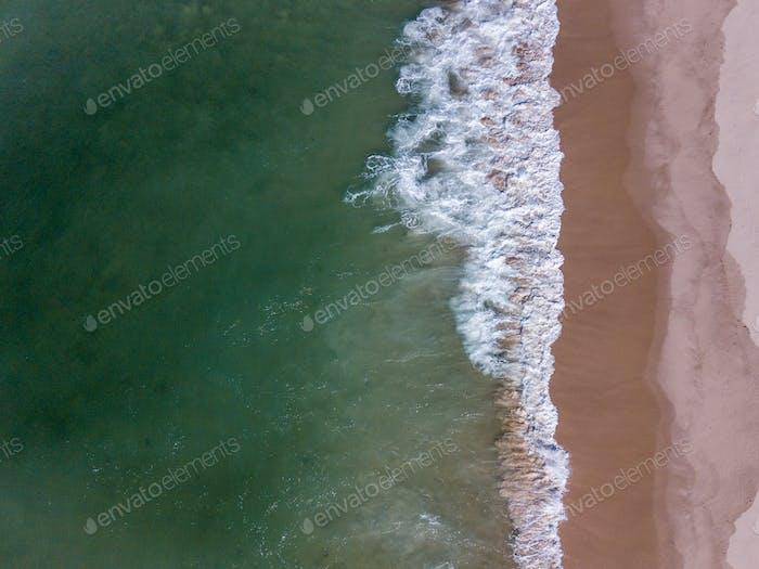 Drohne Bild von Wellen, die den Strand treffen.