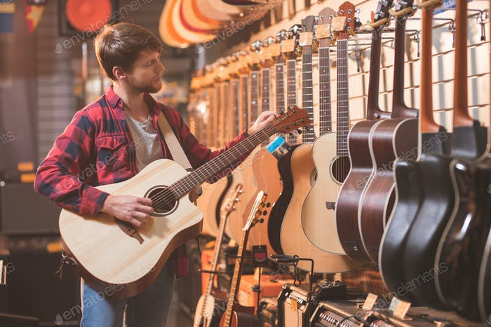 Young man with guitar in a music store