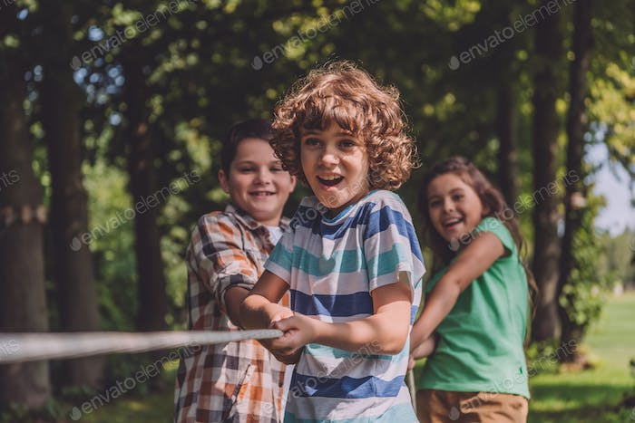 selective focus of cheerful kids competing in tug of war