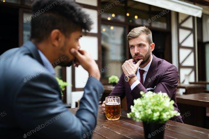 Zwei skeptische Geschäftsleute sprechen auf einem Treffen im Freien