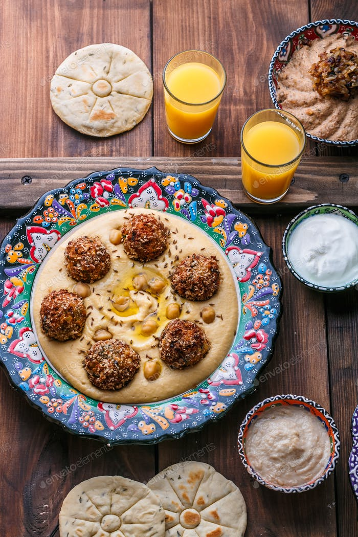 Hummus with falafel and pita in traditional plate
