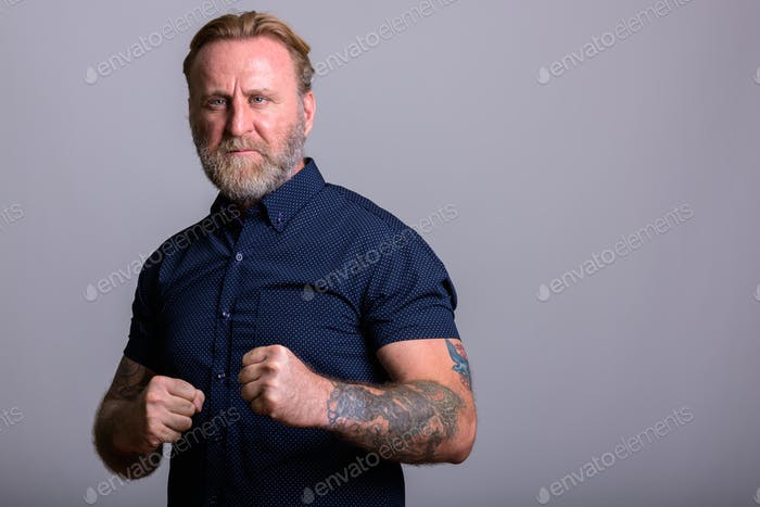 Studio shot of mature bearded man with hand tattoos getting read
