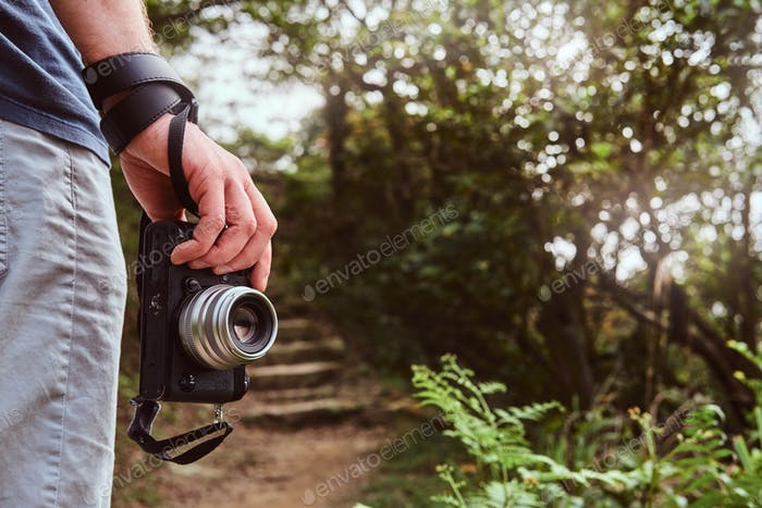Man is holding camera in his hand while walking by the path throw the green mountains