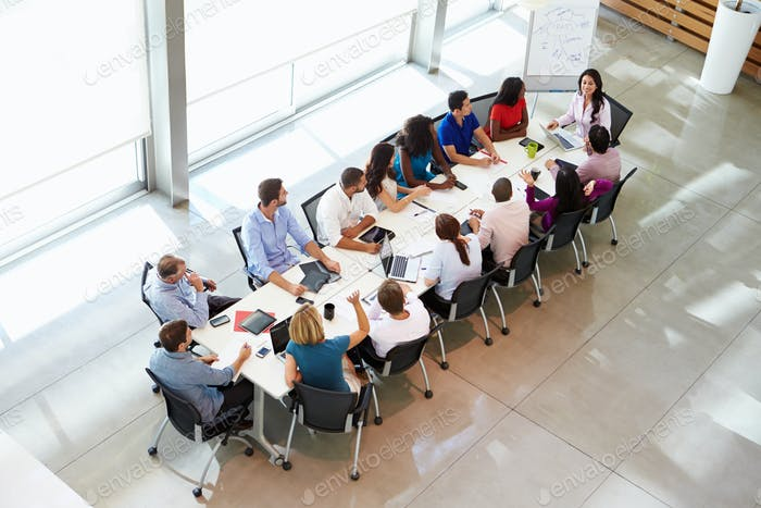 Mujer de negocios de la reunión alrededor de la mesa de la sala de juntas