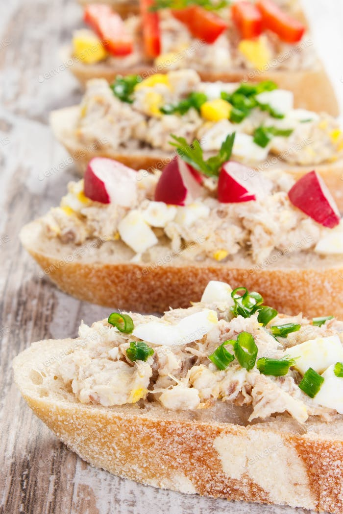 Closeup of crusty baguette with mackerel or tuna fish paste, healthy nutrition