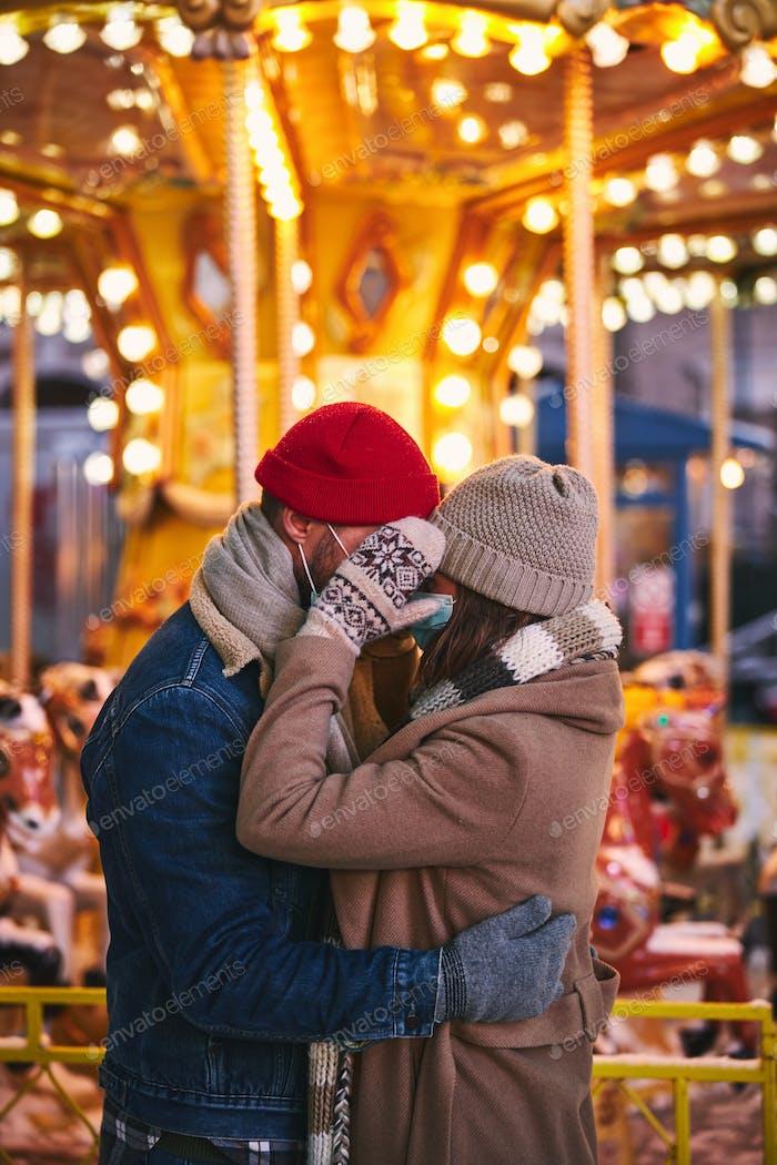 Pareja romántica con máscaras médicas abrazándose en el parque de atracciones