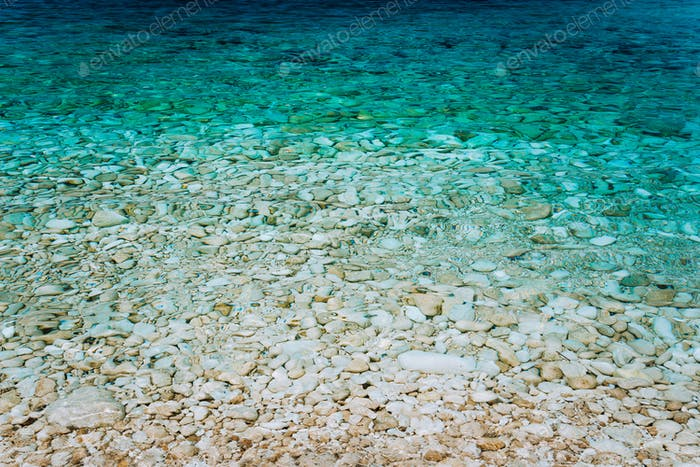 Crystal clear turquoise waters, peaceful bay with calm transparent water surface. Idyllic Summer