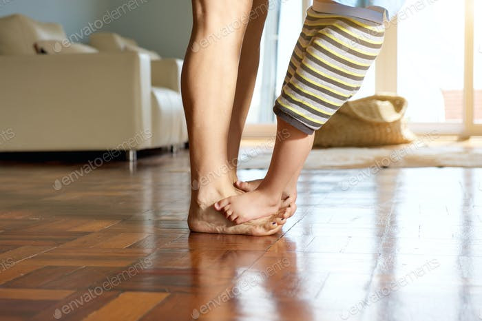 Little boy standing on mother's feet
