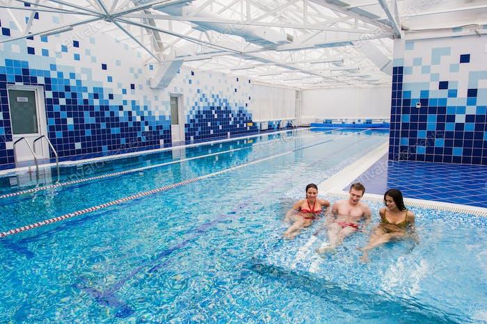 Joyful friends relaxing in swimming pool