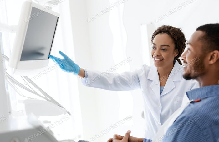 Dentist and patient looking at blank display at clinic