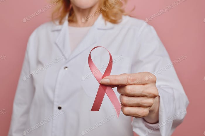 Female Doctor Holding Pink Ribbon Close Up
