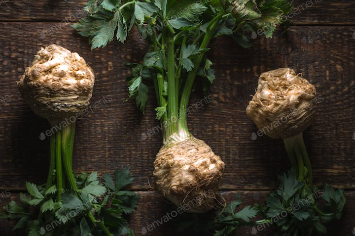 Celery roots with green leaves on brown boards