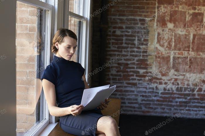 Geschäftsfrau sitzend durch Fenster Dokumente lesen