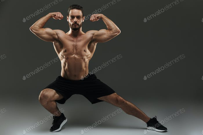 Portrait of a fit muscular bodybuilder flexing biceps