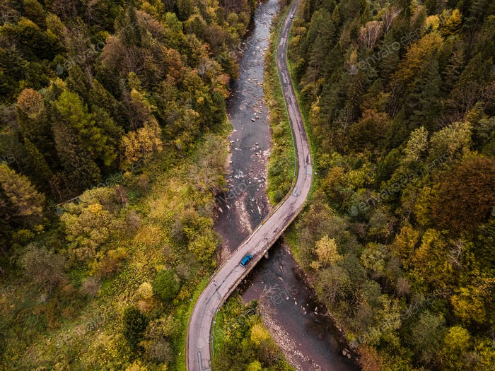 Blue Car Crossing River on Bridge in Forest on Winding Curvy Road.