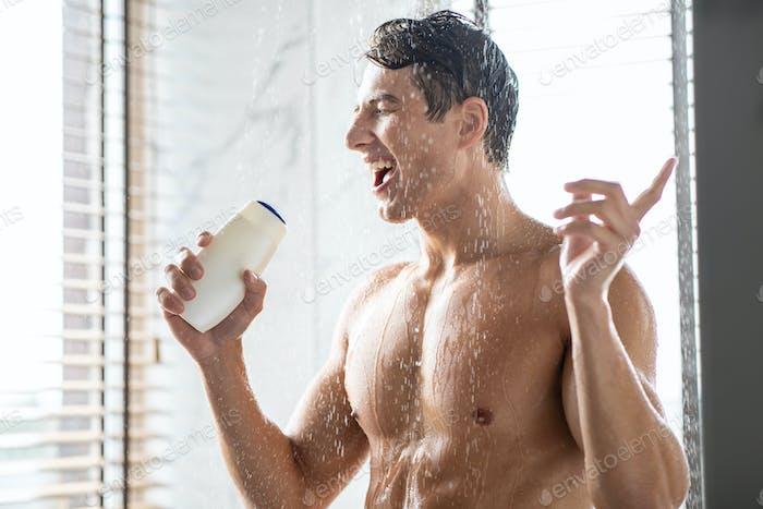 Hübscher junger Mann, der Körper wäscht und in einer Shampo