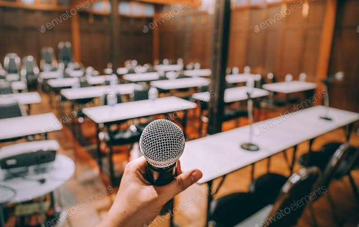 Close-up microphone with blurred people attending seminar background. Vintage process